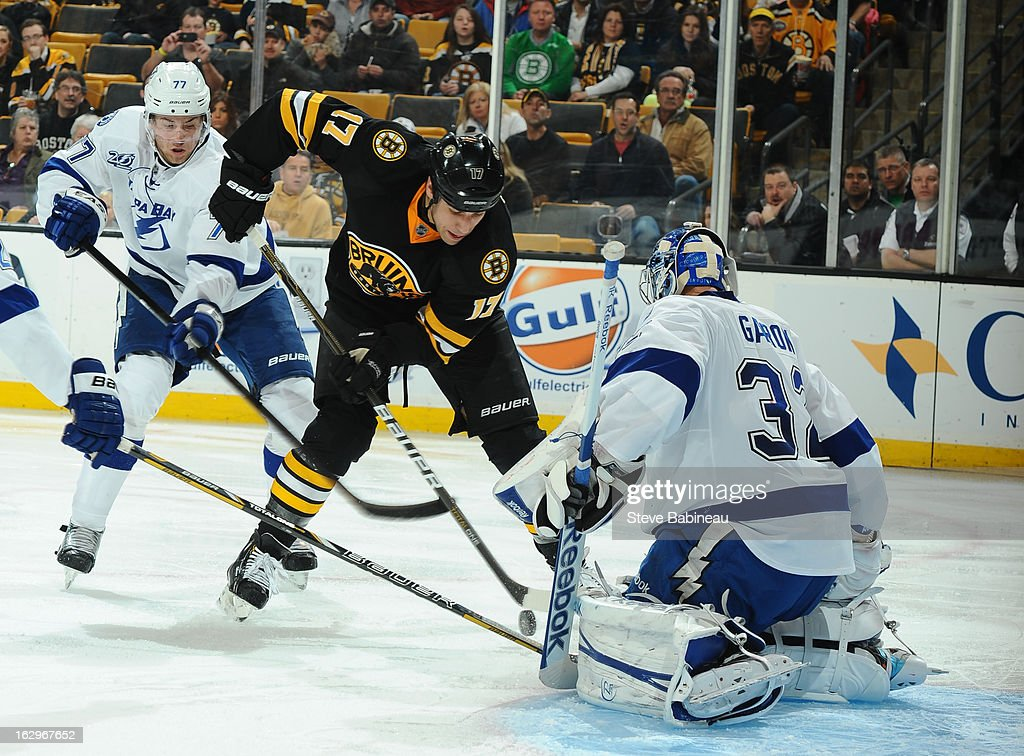 Milan Lucic #17 of the Boston Bruins handles the puck against Mathieu Garon #32 of the Tampa Bay Lightning at the TD Garden on March 2, 2013 in Boston, Massachusetts.