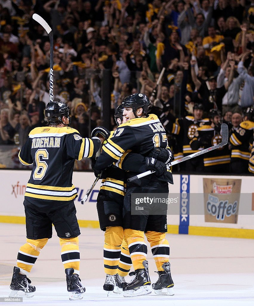 Milan Lucic of the Boston Bruins is congratulated by teammates Dennis Wideman and Andrew Ference after Lucic scored the game winning goal in the...