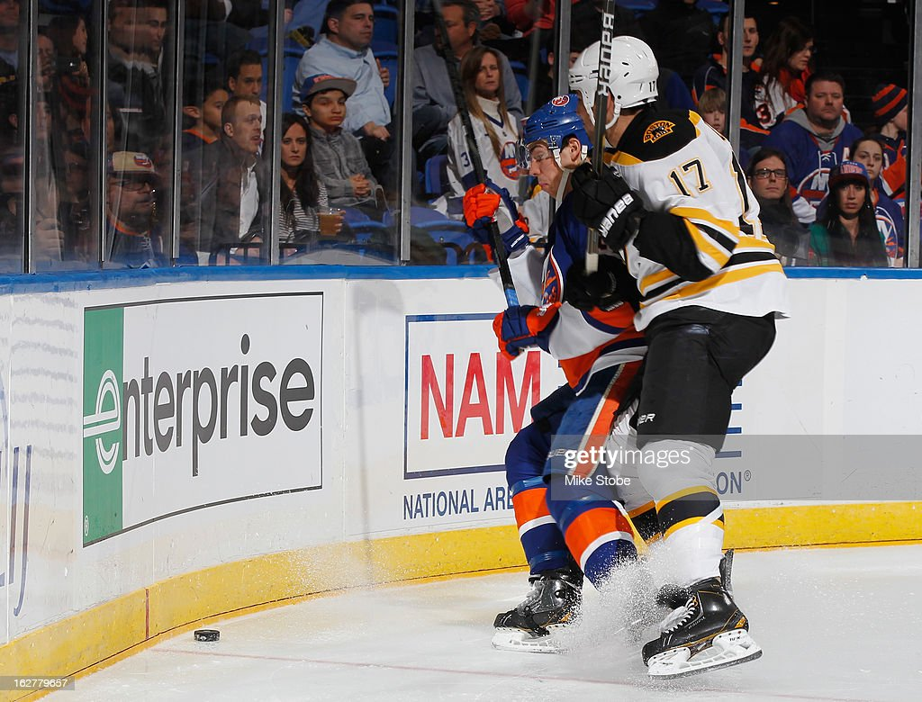 Milan Lucic #17 of the Boston Bruins is held off by Travis Hamonic #3 of the New York Islanders at Nassau Veterans Memorial Coliseum on February 26, 2013 in Uniondale, New York.
