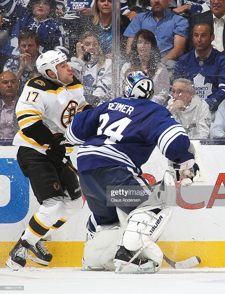 Milan Lucic #17 of the Boston Bruins keeps an eye on a high puck while being checked by James Reimer #34 of the Toronto Maple Leafs in Game Four of the Eastern Conference Quarterfinals during the 2013 NHL Stanley Cup Playoffs on May 8, 2013 at the Air Canada Centre in Toronto, Ontario, Canada. The Bruins defeated the Leafs 4-3 in overtime to take a 3-1 series lead.