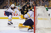 Milan Lucic of the Boston Bruins looks for a shot on goal with pressure from Tyson Strachan of the Buffalo Sabres during the first period at TD...