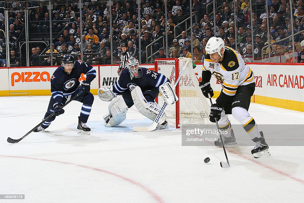 Milan Lucic #17 of the Boston Bruins plays the puck to the side of the net as Paul Postma #4 and goaltender Michael Hutchinson #34 of the Winnipeg Jets defend the goal during second period action at the MTS Centre on April 10, 2014 in Winnipeg, Manitoba, Canada.