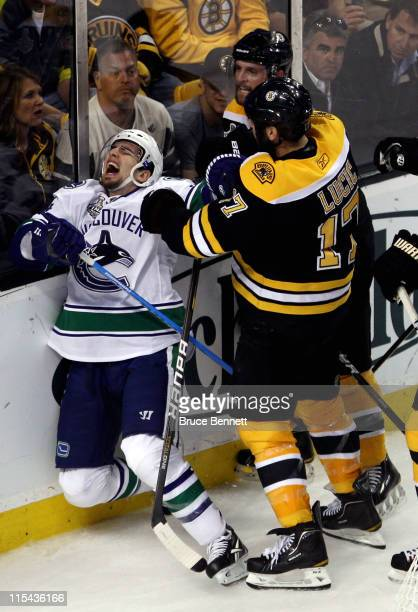 Milan Lucic of the Boston Bruins punches Alex Burrows of the Vancouver Canucks during Game Three of the 2011 NHL Stanley Cup Final at TD Garden on...