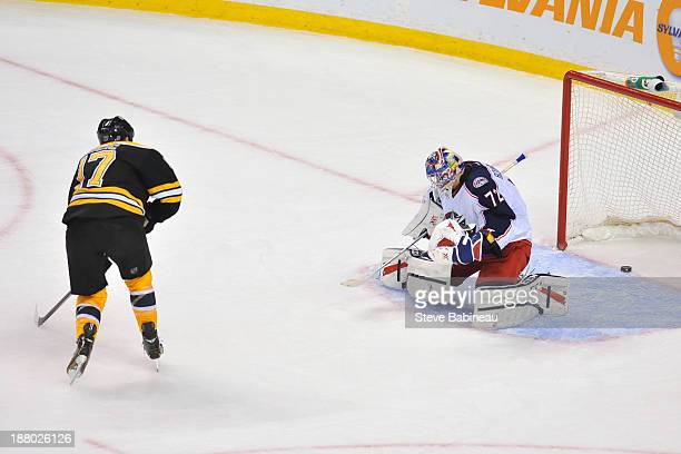 Milan Lucic of the Boston Bruins scores a goal in overtime against Sergei Bobrovsky of the Columbus Blue Jackets at the TD Garden on November 14 2013...
