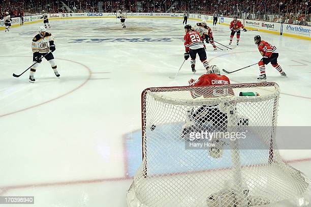 Milan Lucic of the Boston Bruins scores a second period goal against goalie Corey Crawford of the Chicago Blackhawks in Game One of the 2013 NHL...