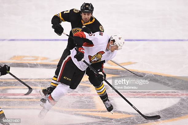 Milan Lucic of the Boston Bruins skates against Patrick Wiercioch of the Ottawa Senators at the TD Garden on December 13 2014 in Boston Massachusetts