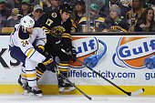Milan Lucic of the Boston Bruins skates against Tyson Strachan of the Buffalo Sabres during the first period at TD Garden on March 17 2015 in Boston...