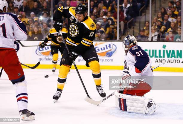 Milan Lucic of the Boston Bruins tips the puck in front of Curtis McElhinney of the Columbus Blue Jackets for a goal in the first period during the...
