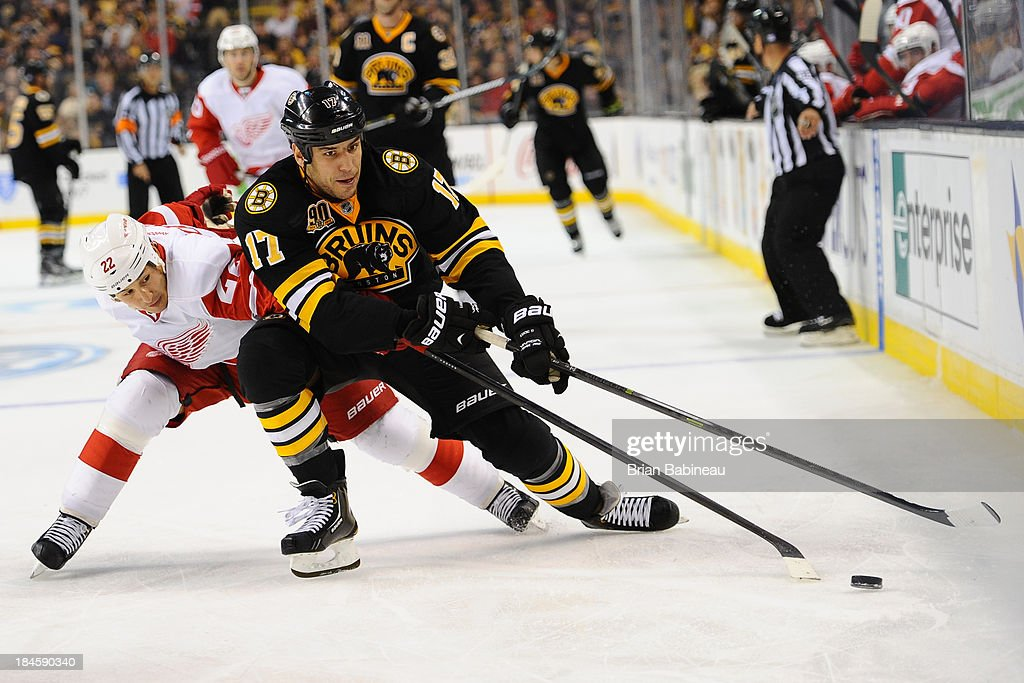 <a gi-track='captionPersonalityLinkClicked' href=/galleries/search?phrase=Milan+Lucic&family=editorial&specificpeople=537957 ng-click='$event.stopPropagation()'>Milan Lucic</a> #17 of the Boston Bruins tries to handle the puck against <a gi-track='captionPersonalityLinkClicked' href=/galleries/search?phrase=Jordin+Tootoo&family=editorial&specificpeople=203013 ng-click='$event.stopPropagation()'>Jordin Tootoo</a> #22 of the Detroit Red Wings at the TD Garden on October 14, 2013 in Boston, Massachusetts.