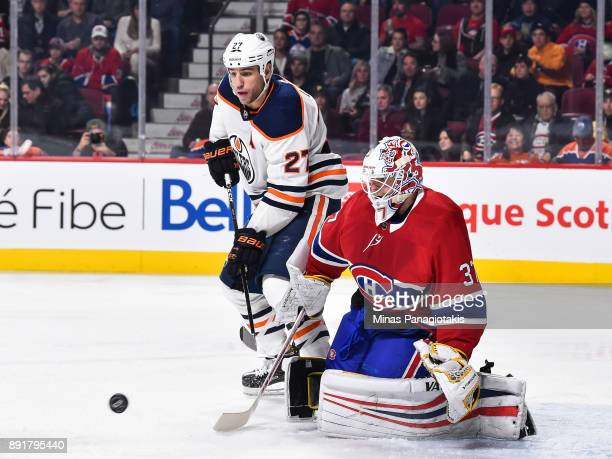 Milan Lucic of the Edmonton Oilers and goaltender Antti Niemi of the Montreal Canadiens watch the puck during the NHL game at the Bell Centre on...