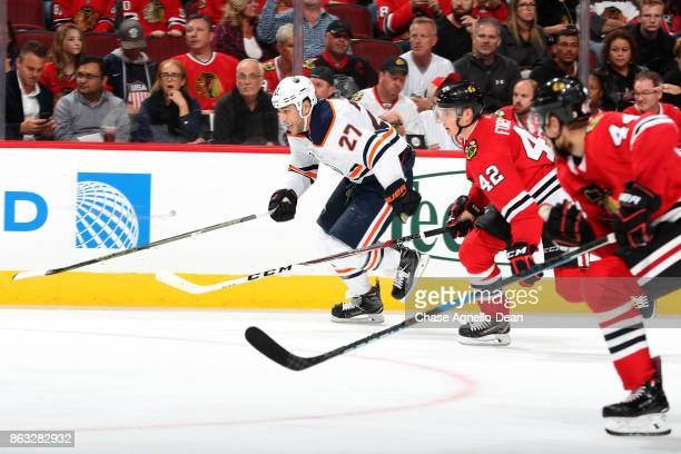 Milan Lucic of the Edmonton Oilers and Gustav Forsling of the Chicago Blackhawks skate up the ice in the third period at the United Center on October...