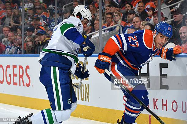 Milan Lucic of the Edmonton Oilers battles for the puck against Luca Sbisa of the Vancouver Canucks on October 8 2016 at Rogers Place in Edmonton...