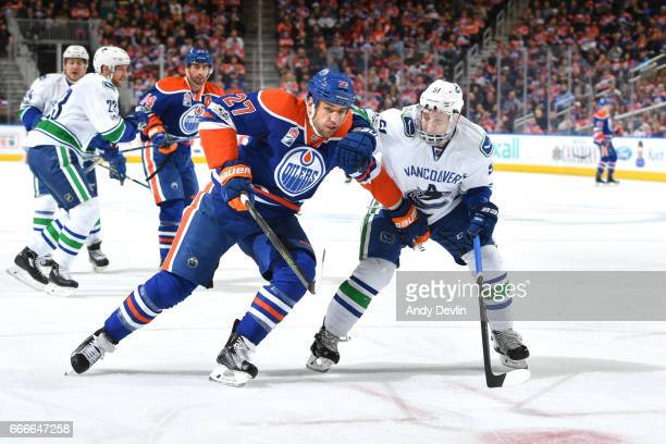 Milan Lucic of the Edmonton Oilers battles for the puck against Troy Stecher of the Vancouver Canucks on April 9 2017 at Rogers Place in Edmonton...