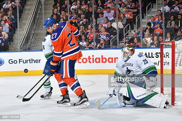 Milan Lucic of the Edmonton Oilers battles for the puck during the game against Chris Tanev the Vancouver Canucks in front of net minder Jacob...