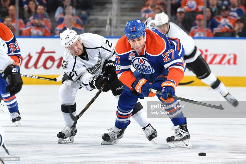 Milan Lucic #27 of the Edmonton Oilers skates with the puck while being pursued by Trevor Lewis #22 of the Los Angeles Kings on March 20, 2017 at Rogers Place in Edmonton, Alberta, Canada.