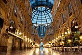 Symmetrical night shot of the famous Galleria Vittorio Emanuele II in Milan, Italy, showing the spectacular view of an almost golden gate to luxury