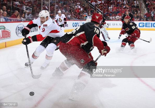 Milan Michalek of the Ottawa Senators attempts to control the puck pressured by Rostislav Klesla of the Phoenix Coyotes during the second period of...