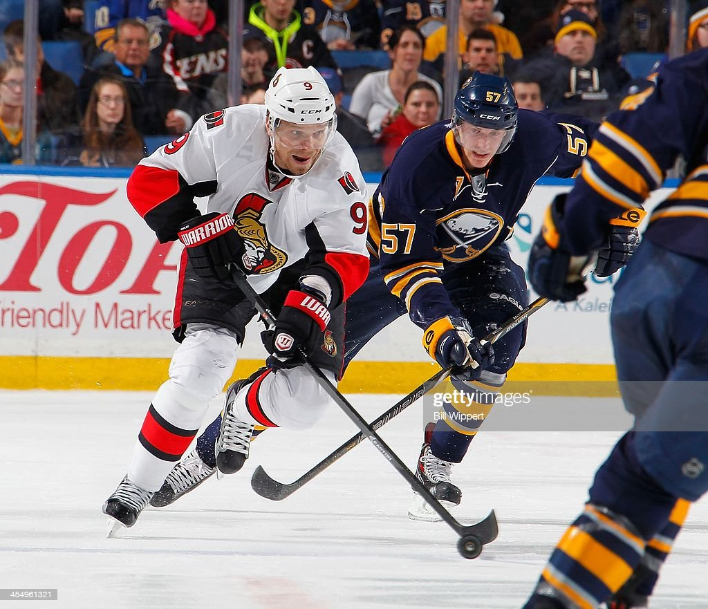 Milan Michalek #9 of the Ottawa Senators controls the puck against Tyler Myers #57 of the Buffalo Sabres on December 10, 2013 at the First Niagara Center in Buffalo, New York.