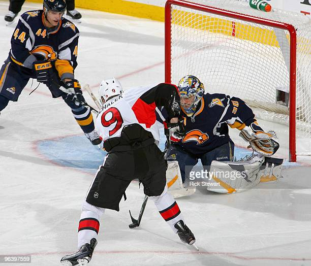 Milan Michalek of the Ottawa Senators dekes Ryan Miller of the Buffalo Sabres but can't get a shot off as Andrej Sekera of the Sabres watches at HSBC...