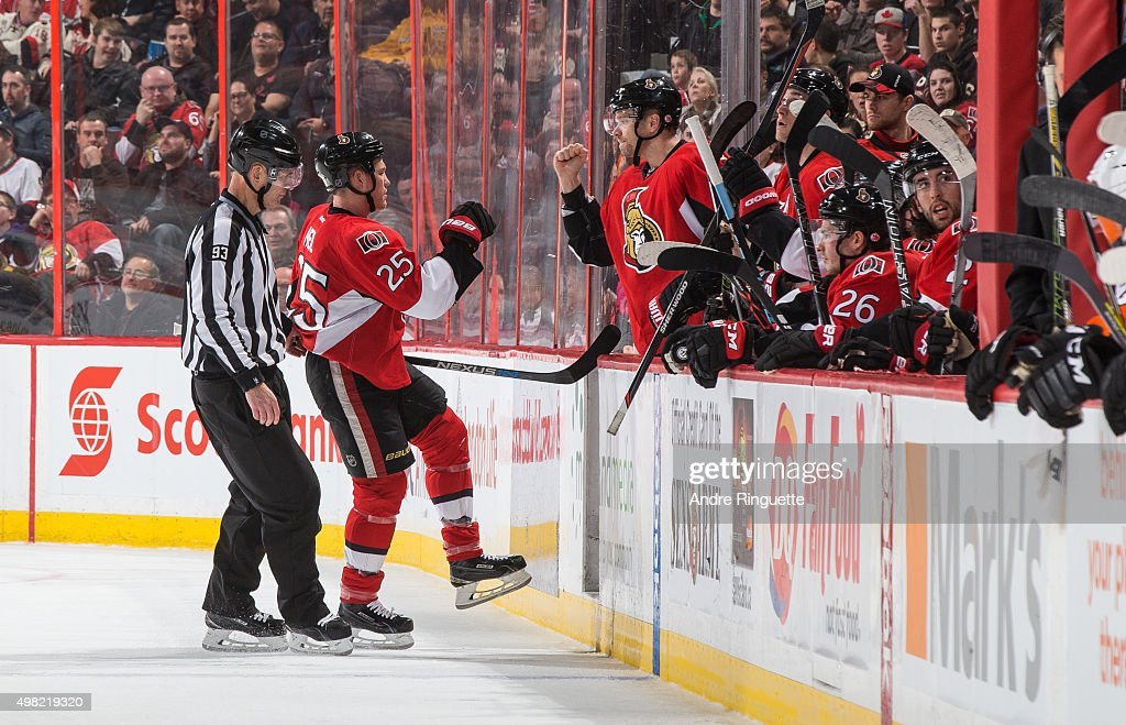 Milan Michalek of the Ottawa Senators fistbumps Chris Neil after a fight in a game against the Philadelphia Flyers as Neil is escorted to the bench...