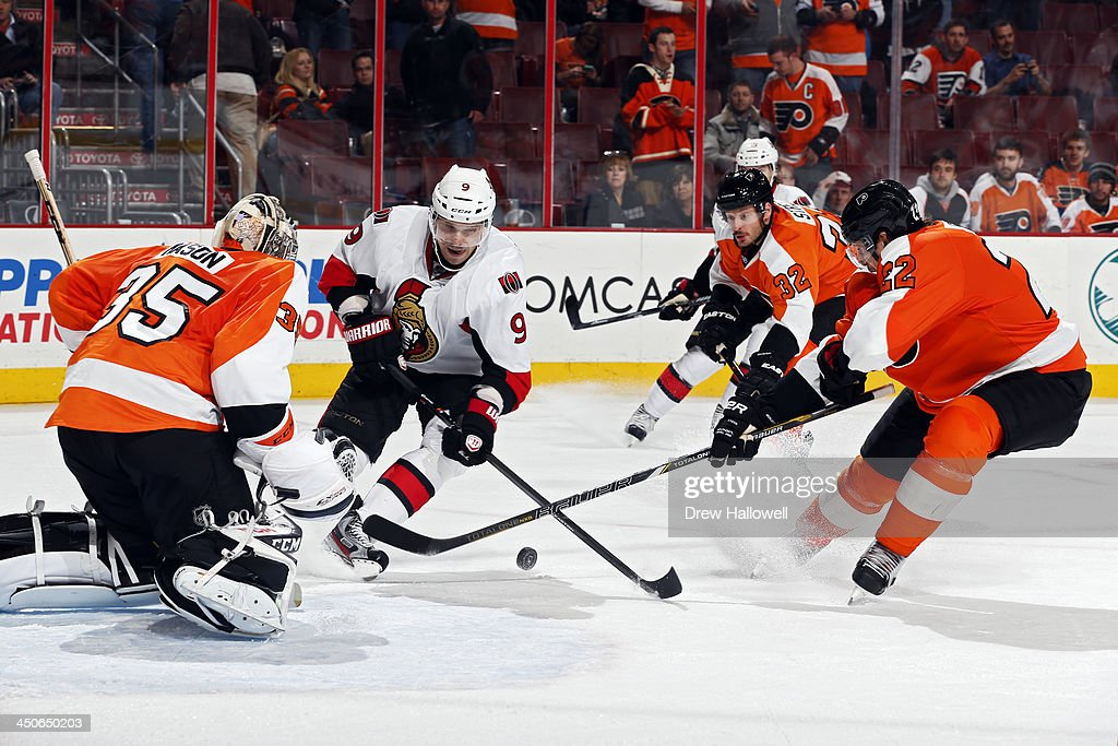 <a gi-track='captionPersonalityLinkClicked' href=/galleries/search?phrase=Milan+Michalek&family=editorial&specificpeople=544987 ng-click='$event.stopPropagation()'>Milan Michalek</a> #9 of the Ottawa Senators gets stick checked by <a gi-track='captionPersonalityLinkClicked' href=/galleries/search?phrase=Luke+Schenn&family=editorial&specificpeople=4254202 ng-click='$event.stopPropagation()'>Luke Schenn</a> #22 of the Philadelphia Flyers as he skates the puck in on Steve Mason #35 at the Wells Fargo Center on November 19, 2013 in Philadelphia, Pennsylvania. The Flyers won 5-2.