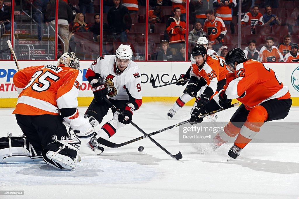 Milan Michalek #9 of the Ottawa Senators gets stick checked by Luke Schenn #22 of the Philadelphia Flyers as he skates the puck in on Steve Mason #35 at the Wells Fargo Center on November 19, 2013 in Philadelphia, Pennsylvania. The Flyers won 5-2.