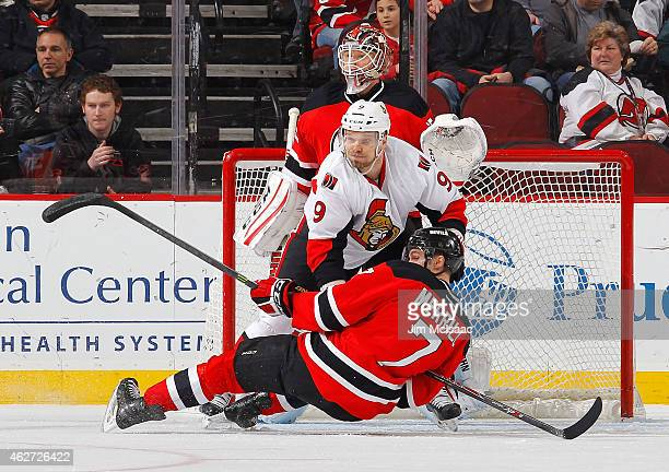 Milan Michalek of the Ottawa Senators knocks down Jon Merrill of the New Jersey Devils in front of Senators goalie Cory Schneider during the second...