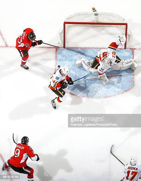 Milan Michalek of the Ottawa Senators scores a goal as Ales Hemsky takes position against Chris Butler and Karri Ramo of the Calgary Flames during an...