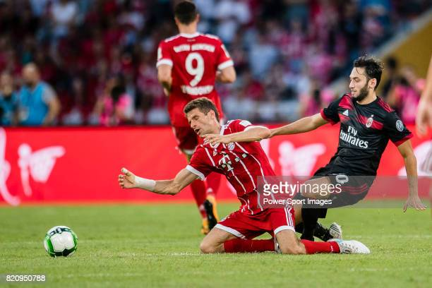 Milan Midfielder Hakan Calhanoglu trips up with Bayern Munich Forward Thomas Muller during the 2017 International Champions Cup China match between...