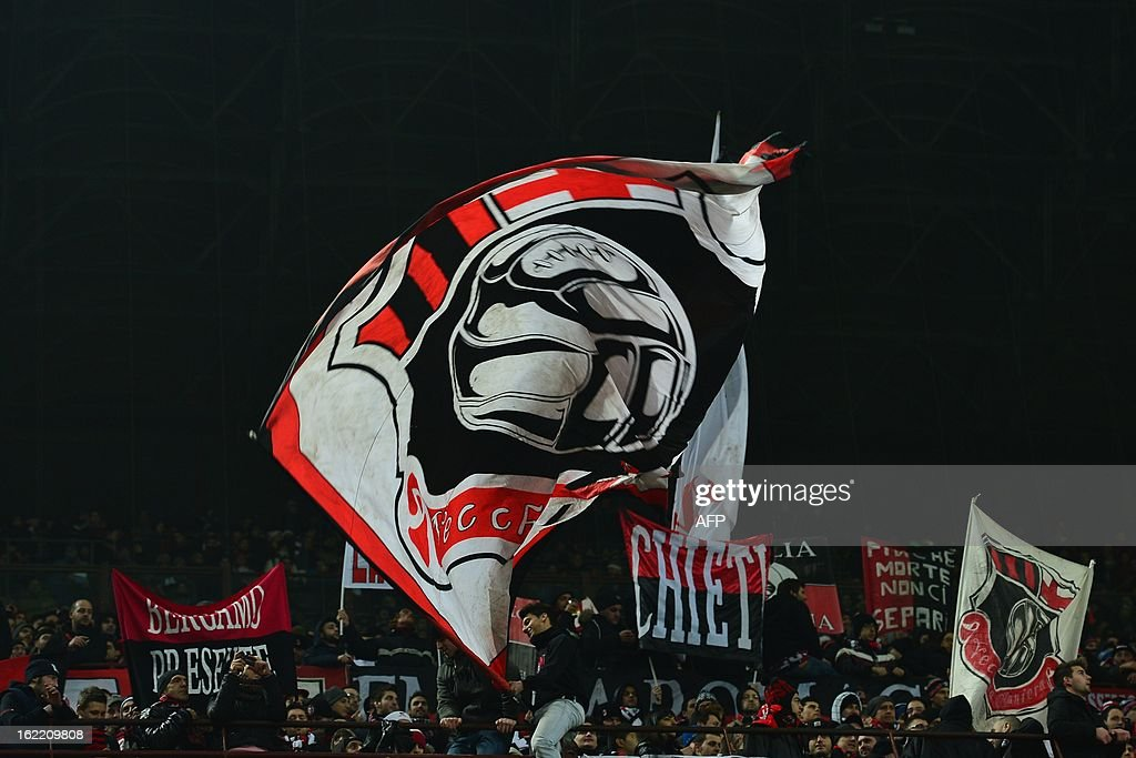 AC Milan supporters cheer their team by waving flags prior the Champions League football match between AC Milan and FC Barcelona on February 20, 2013 at San Siro Stadium in Milan.
