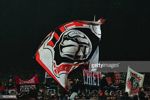 AC Milan supporters cheer their team by waving flags prior the Champions League football match between AC Milan and FC Barcelona on February 20 2013...