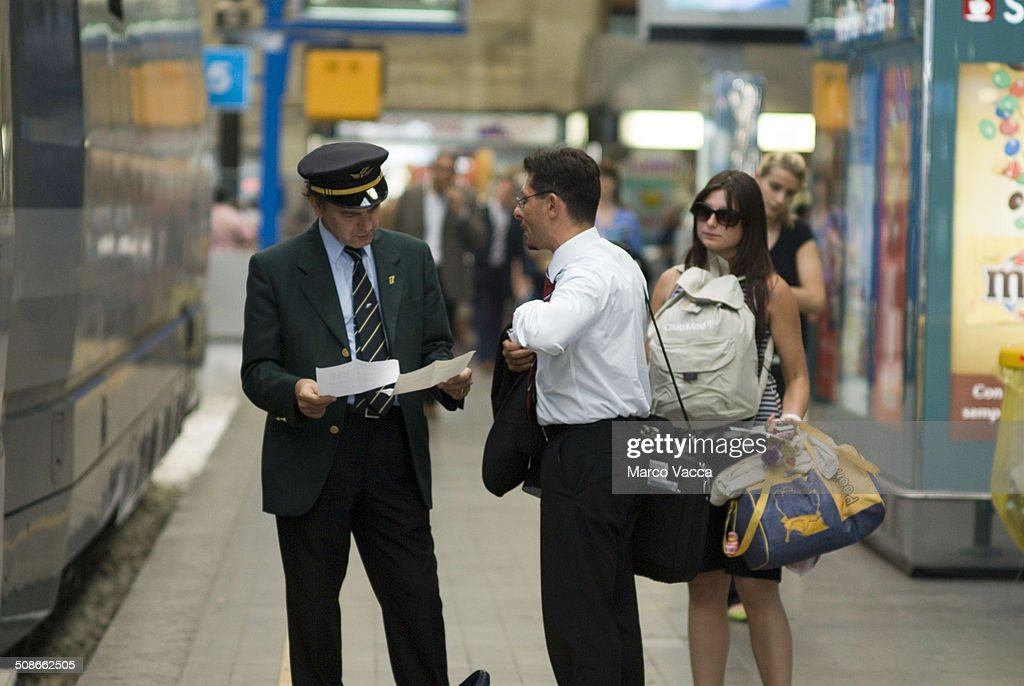 a man smartly dressed asks for direction to a train conductor, on the back a woman covered with luggages waits to do the same