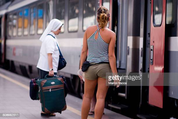 a nun holding her luggage a girl smoking and dressed with short and sleeveless shirt wait to enter a train