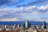 The wonderful panorama of the Milan skyline with a blue sky and low clouds, the bright light of a clear day allows you to see the mountains of the Alps Group