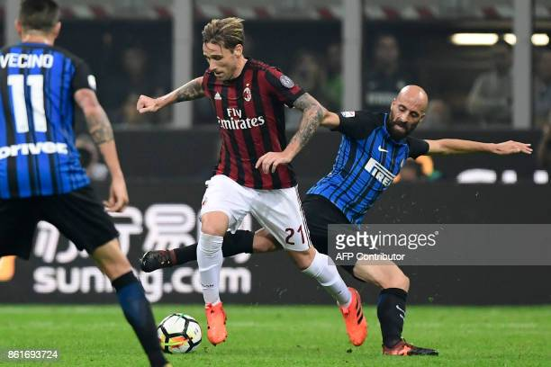 AC Milan's Argentinian midfielder Lucas Biglia is tackled by Inter Milan's Spanish midfielder Iglesias Borja Valero during the Italian Serie A...
