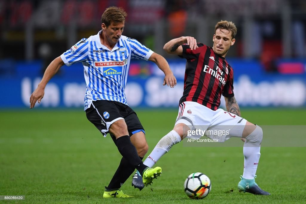 AC Milan's Argentinian midfielder Lucas Biglia (R) vies with Spal's Itlian midfielder Eros Schiavon during the Italian Serie A football match AC Milan vs Spal at San Siro stadium in Milan on September 20, 2017. /