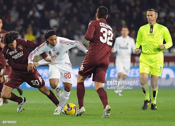 AC Milan's Brazilian forward Ronaldinho fights for the ball with Torino's defender Francesco Pratali and defender Riccardo Colombo as referee Stefano...