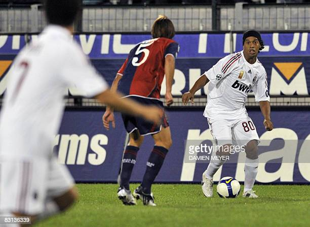 AC Milan's Brazilian forward Ronaldinho prepares to pass the ball to teammate Brazilian forward Pato past Cagliari's midfielder Daniele Conti during...