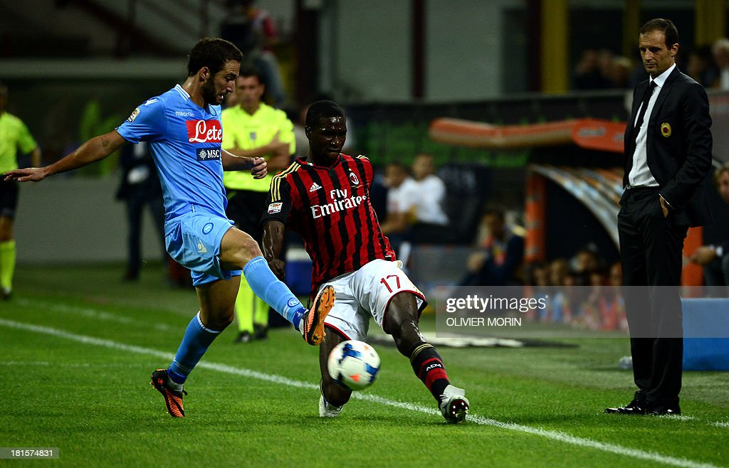 AC Milan's Colombian defender Cristian Zapata (R) fights for the ball with Napoli's Argentinian forward Gonzalo Gerardo Higuain during the seria A football match AC Milan vs Naples, on septembre 22, 2013, in San Siro stadium in Milan.
