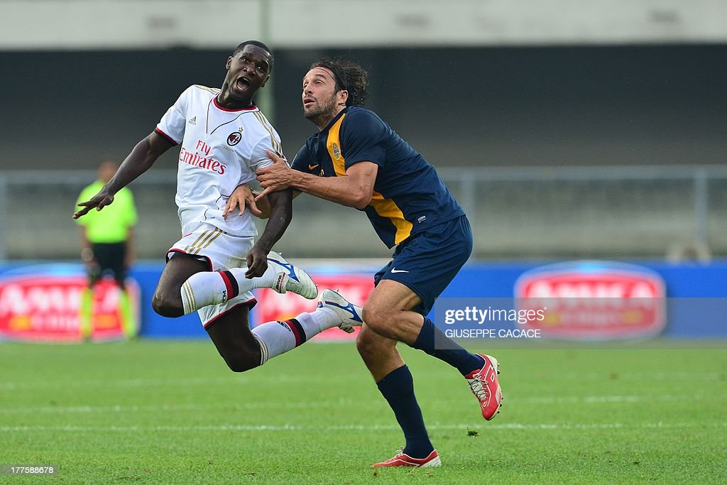 AC Milan's Colombian defender Cristian Zapata (L) is tackled by Hellas Verona's forward Luca Toni during the Serie A football match Hellas Verona vs. AC Milan at Bentegodi Stadium in Verona on August 24, 2013.