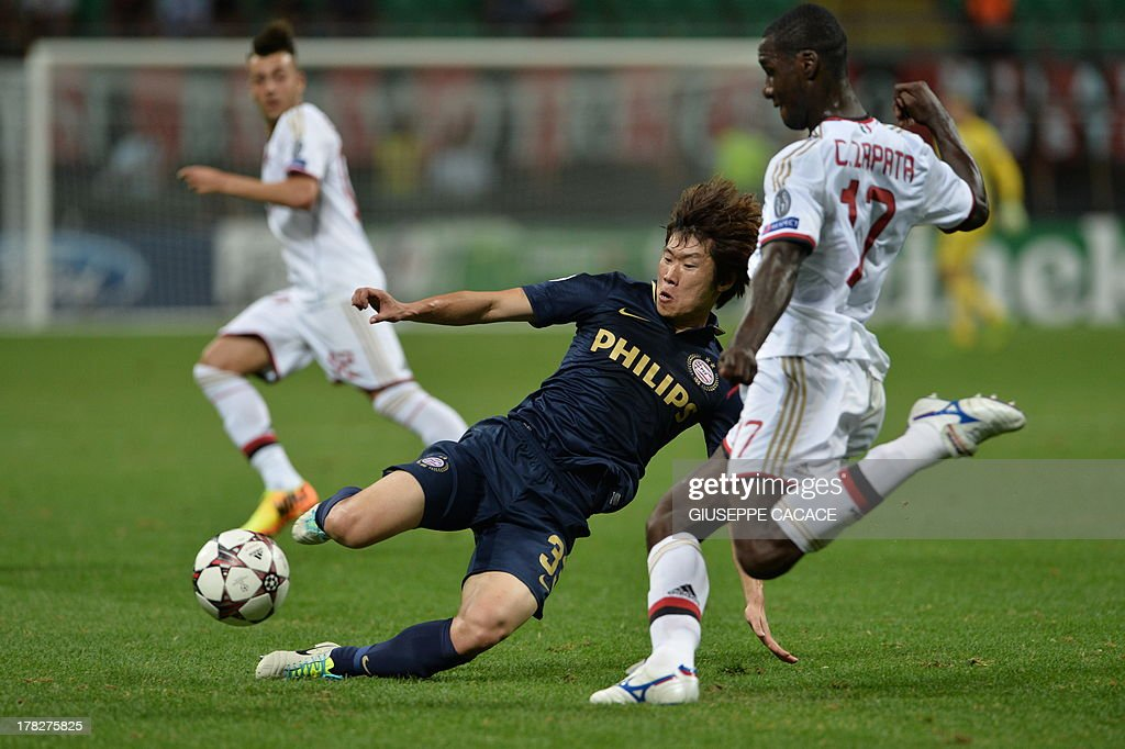 AC Milan's Colombian defender Cristian Zapata (R) vies for the ball with PSV Eindhoven's South Korean midfielder Park Ji Sung during the Champions League preliminary round football match between AC Milan and PSV Eindhoven, on August 28, 2013 in San Siro Stadium. AFP PHOTO / GIUSEPPE CACACE