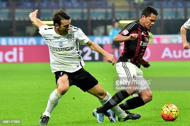 AC Milan's Colombian forward Carlos Bacca challenges Atalanta's Italian defender Gianpaolo Bellini during the Serie A football match between AC Milan...
