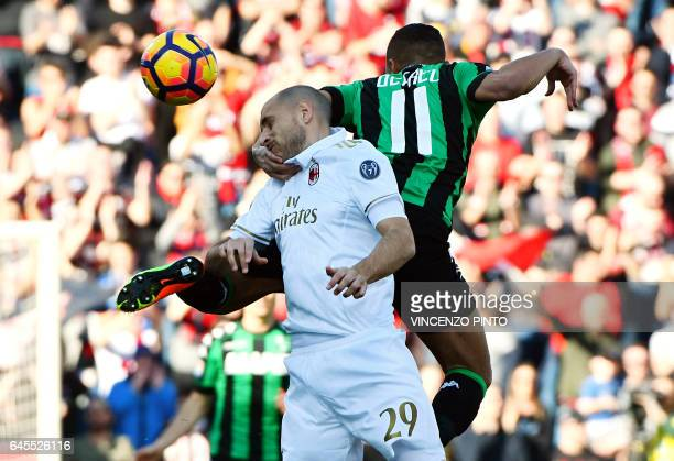 TOPSHOT Milan's defender Gabriel Paletta jumps for the ball next to Sassuolo's forward Gregoire Defrel during the Italian Serie A football match...