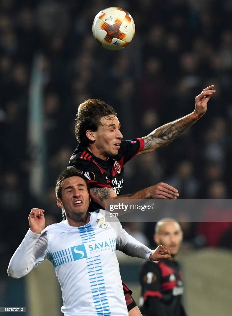 AC Milan's defender Lucas Biglia (R) fights for the ball with Rijeka's midfielder Mario Gavranovic during the UEFA Europa League Group D football match between HNK Rijeka and AC Milan at The Rujevica Stadium in Rijeka on December 7, 2017. /