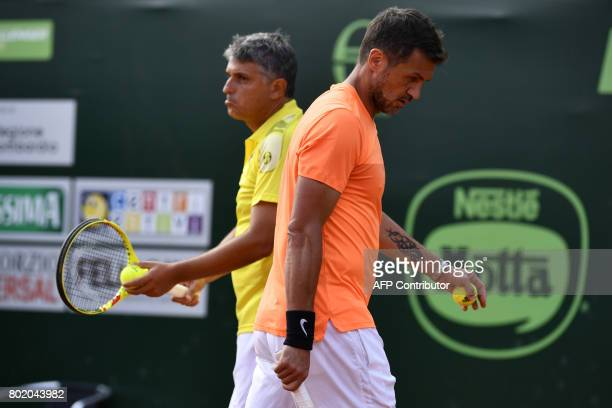 AC Milan's former player Paolo Maldini passes his partner Stefano Landonio during the men's doubles tennis match against Poland's player Tomasz...