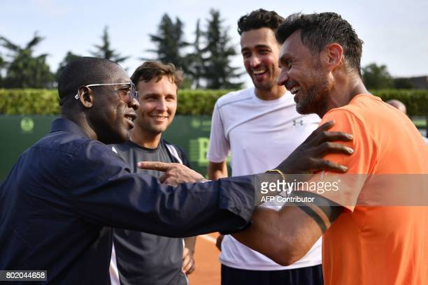 AC Milan's former player Paolo Maldini speaks with AC Milan's former player Clarence Seedor after the men's doubles tennis match with his partner...