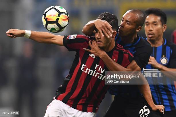 AC Milan's forward Andre Silva from Portugal fights for the ball with Inter Milan's defender Joao Miranda de Souza Filho from Brazil during the...