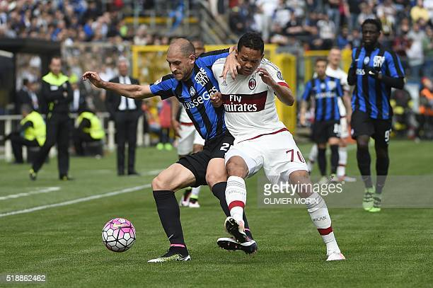 AC Milan's forward from Colombia Carlos Bacca fights for the ball with Atalanta's defender from Italy Ricardo Paletta during the Italian Serie A...