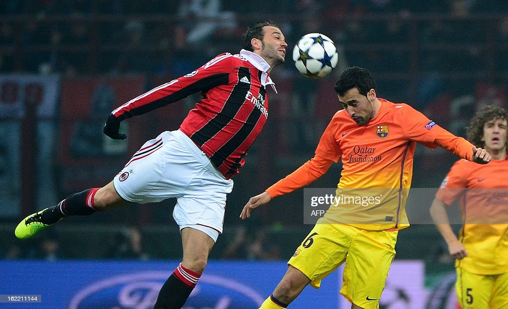 AC Milan's forward Giampaolo Pazzini (L) fights for the ball with Barcelona's midfielder Sergio Busquets during the Champions League football match between AC Milan and FC Barcelona on February 20, 2013 at San Siro Stadium in Milan.