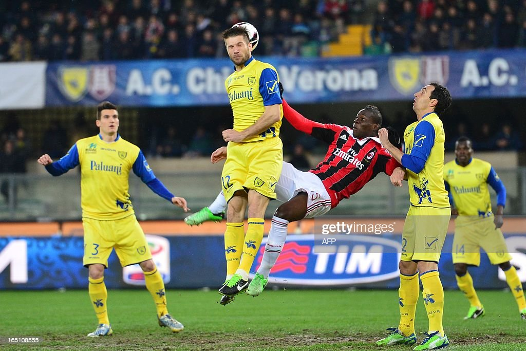 AC Milan's forward Mario Balotelli (Back) fights for the ball with Chievo's Slovenian defender Bostjan Cesar during the Serie A football match between Chievo and AC Milan at the 'Bentegodi Stadium' in Verona on March 30, 2013.